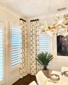 modern curtains hung on dark, round medallions beside window