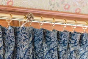 Elegant curtain rod and rings supporting custom drapery in Dallas